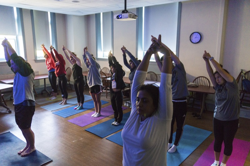 Students in a religion class practice yoga