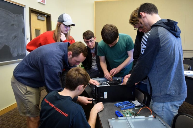 A group of students in Kristopher Micinski's class takes apart a computer in class.