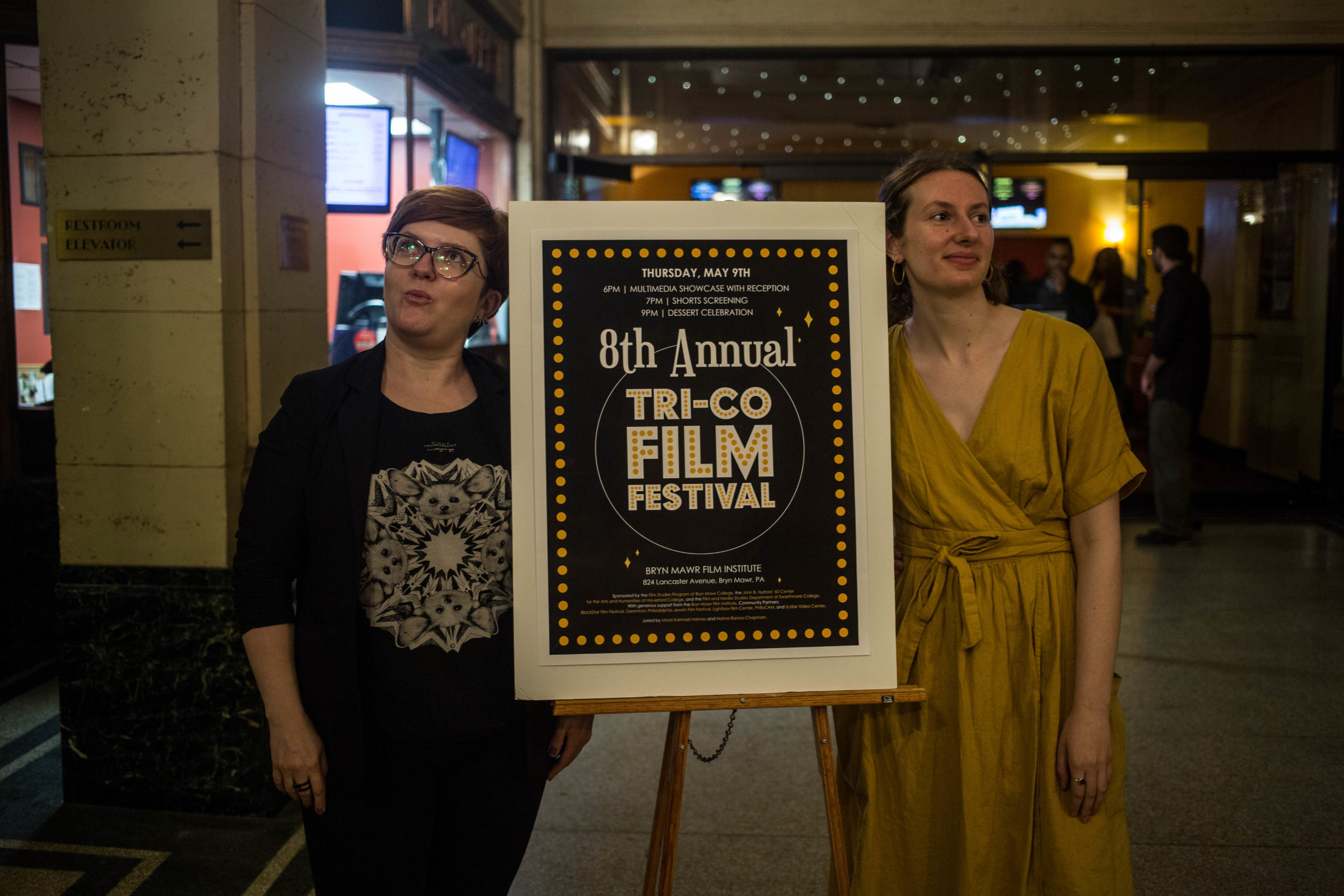 Tri-Co Film Festival Co-directors Dajana Denes Walters and Sophia Abraham-Raveson '18 stand in front of the entrance to Bryn Mawr Film Institute with a poster of the festival.