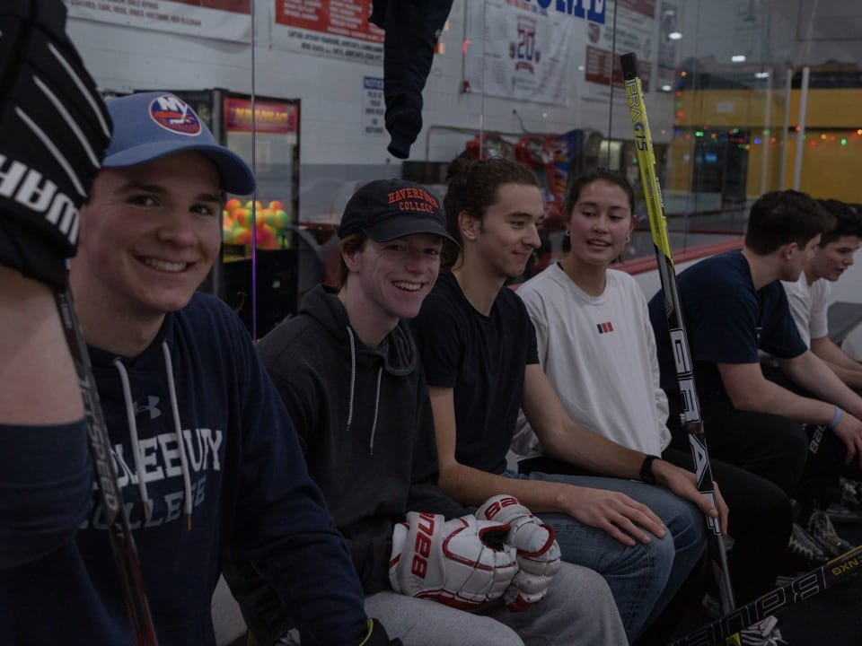 Jackson Bayer, Freddie Gould, Will Harris-Braun, Turner Johnson, Louis Braun, and Ethan Donlon on the bench at the ice hockey rink.