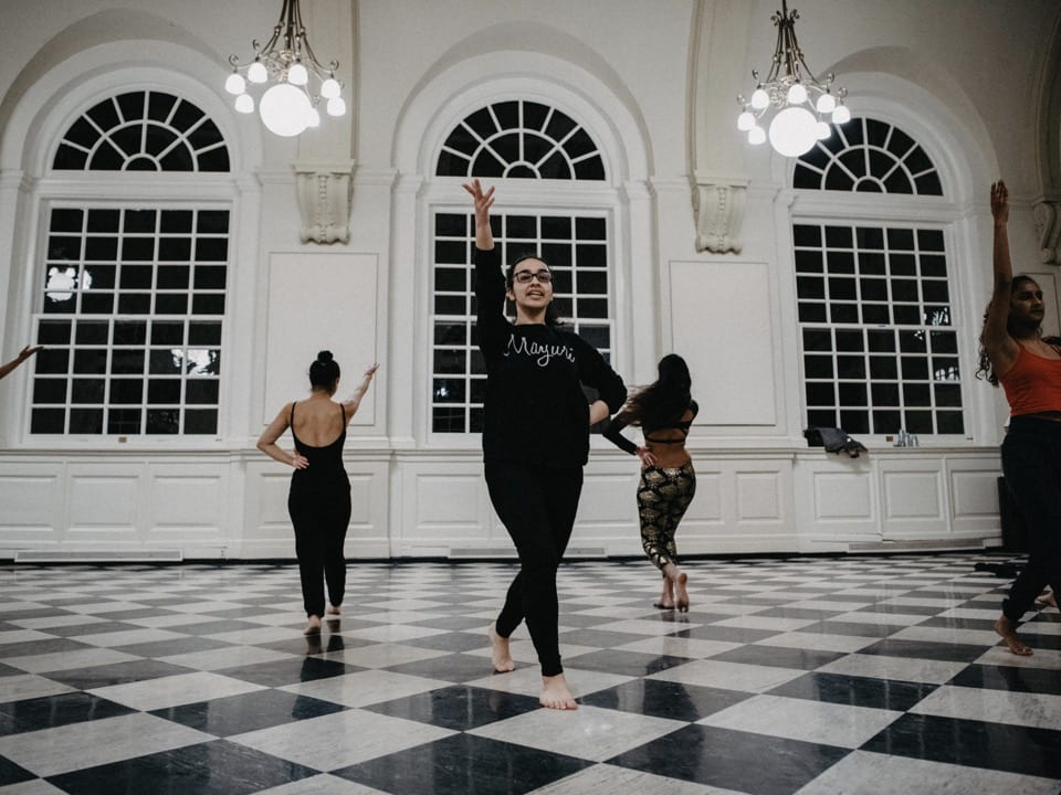 The South Asian fusion dance group practices in Founders Great Hall