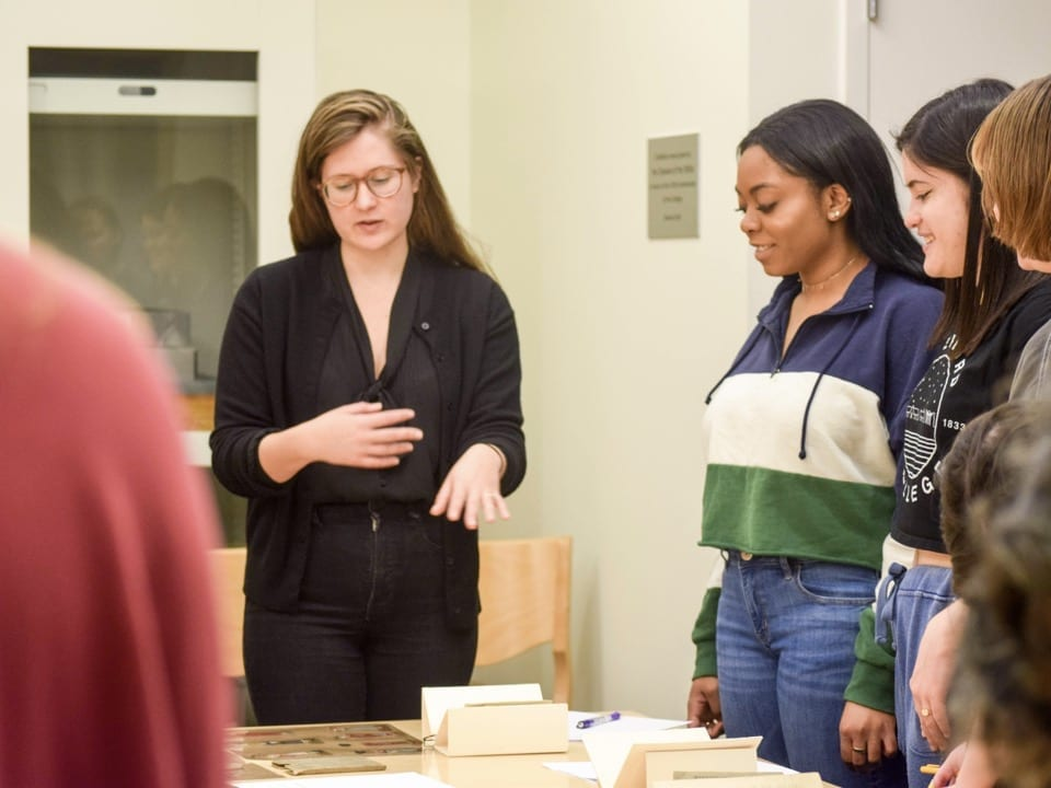 Rosetta Young speaks to students in her class as they look at vintage children's books on a table in Bryn Mawr College's library.