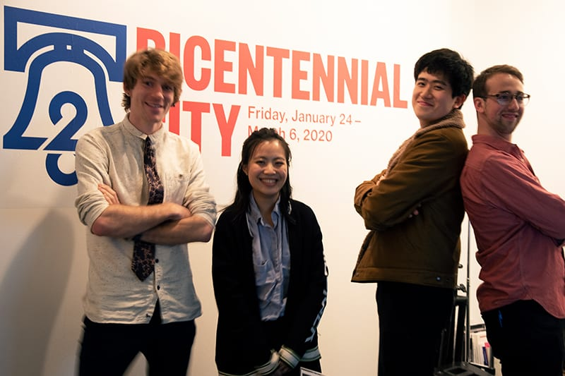 Four of the student filmmakers stand in front of the wall with the exhibit's name on it