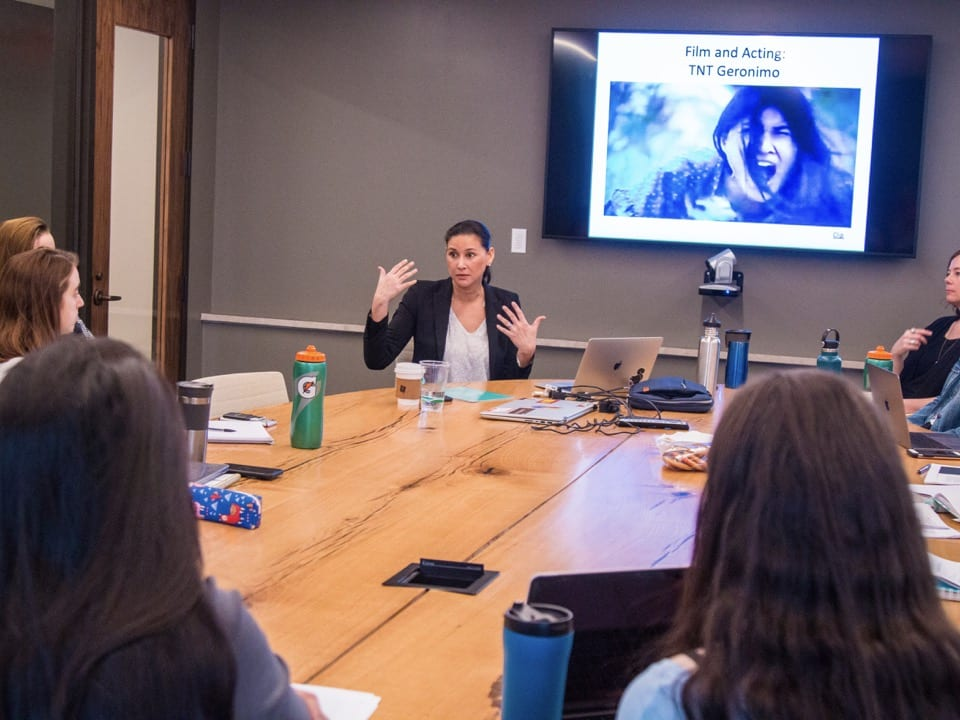 Tailinh Agoyo speaks to the class, seated around a seminar table, with an image from TNT's Geronimo on a screen behind her.