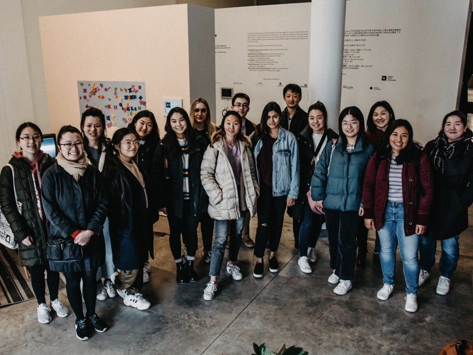 16 students pose in front of the exhibit wall