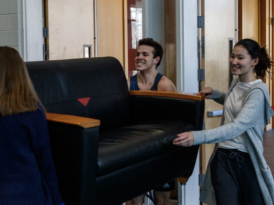 Students move a couch into the GIAC for Plenary.