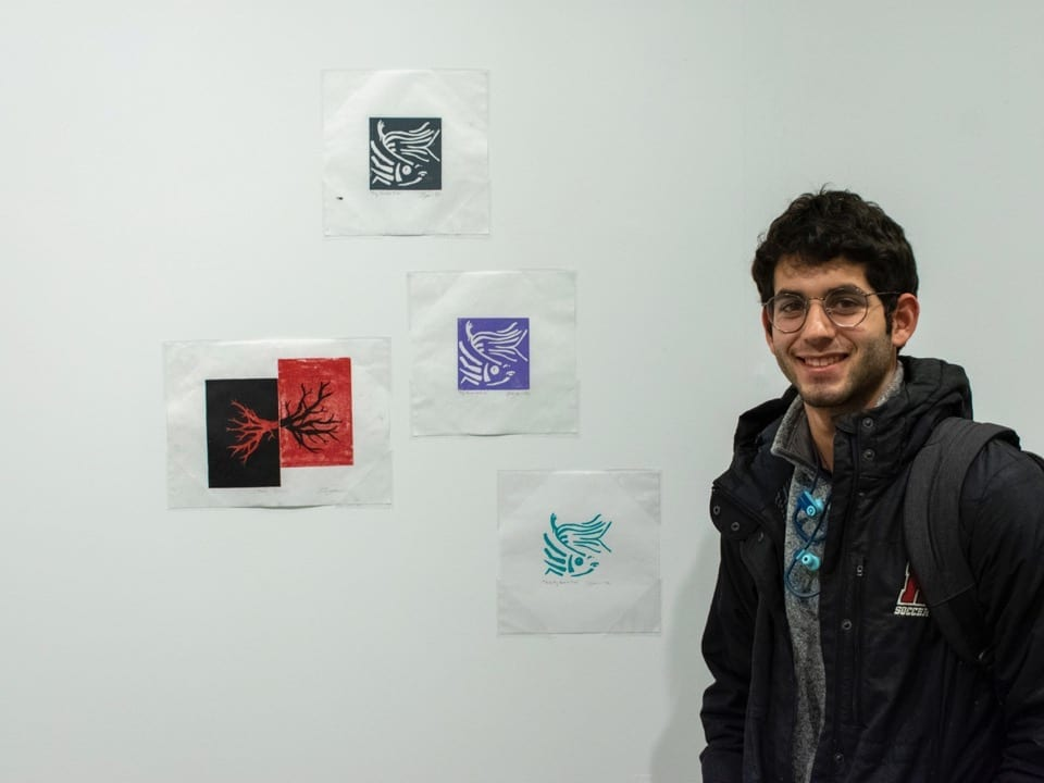 A student artist stands in front of prints pinned to a wall