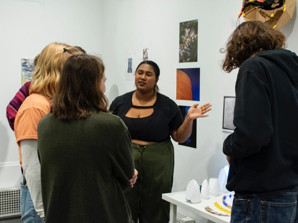 A student presents an art display to a group of students