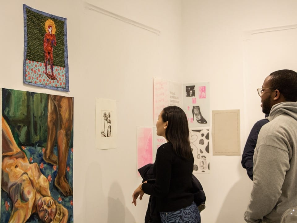 Two students look at a display including a large painting