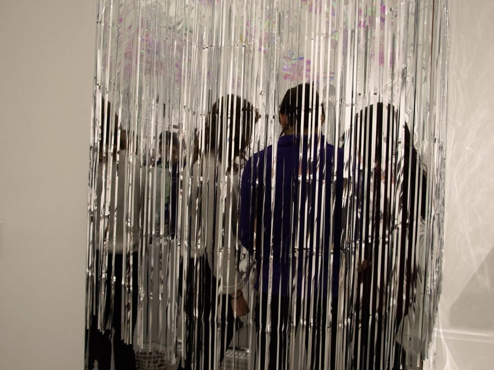 A group of students view art behind a curtain of silver streamers