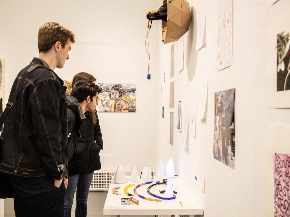 A group of students inspect an art display
