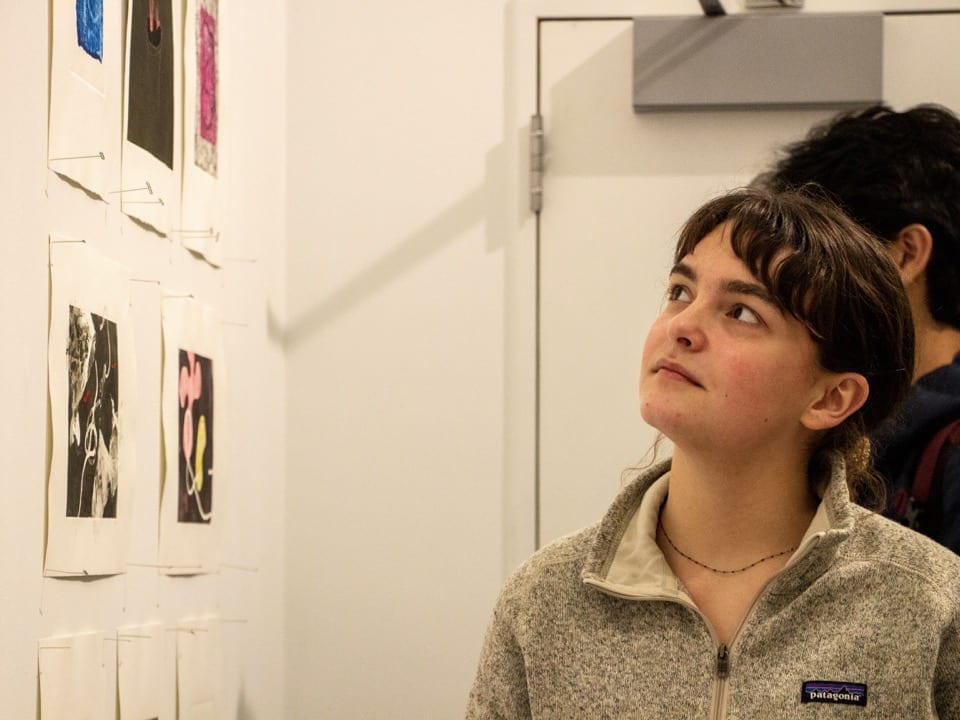 A student looks at art pinned to the wall of the gallery