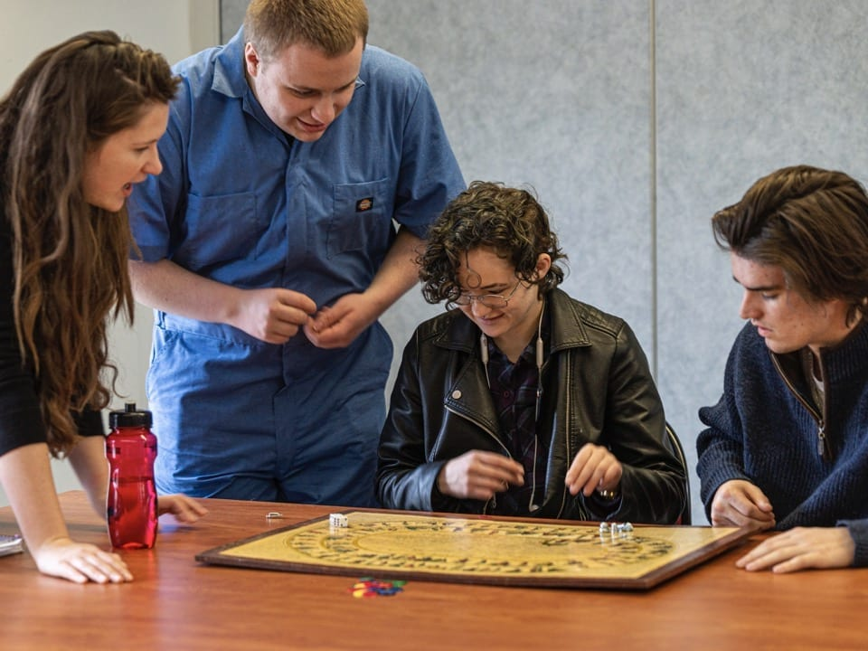 Rosetta Young and her students hover over a vintage Life game board from the 18th century