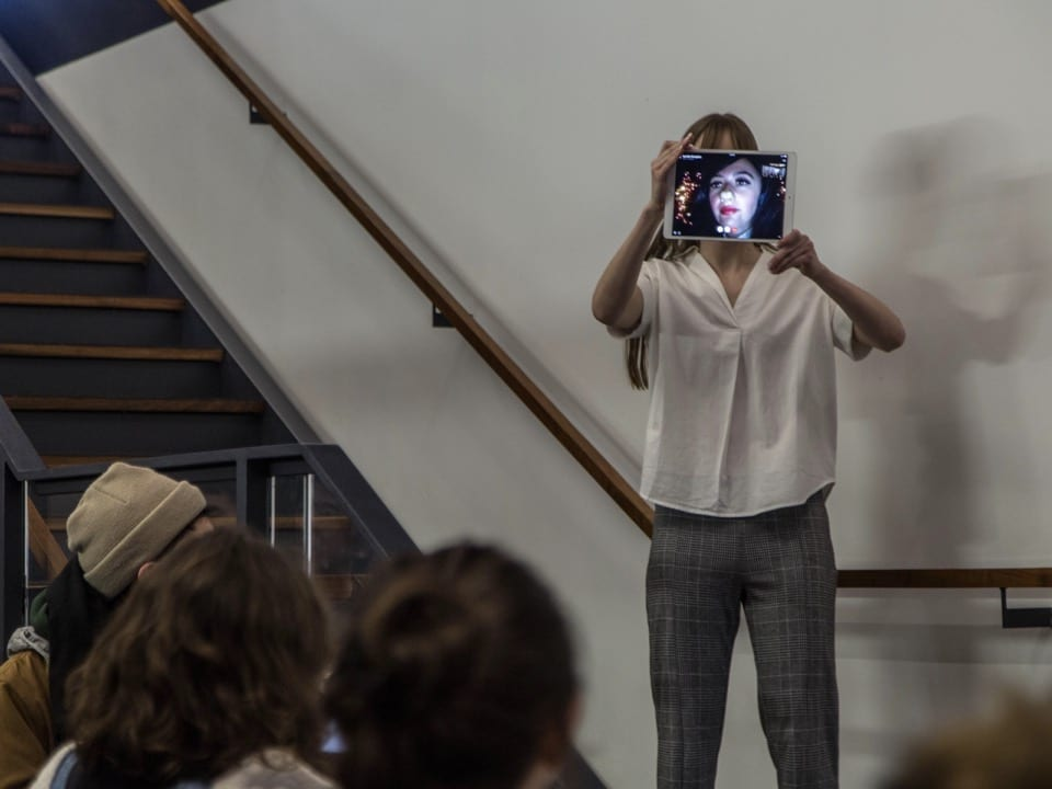 The curator holds an iPad over her face with artist Korallia Stergides on the screen in character
