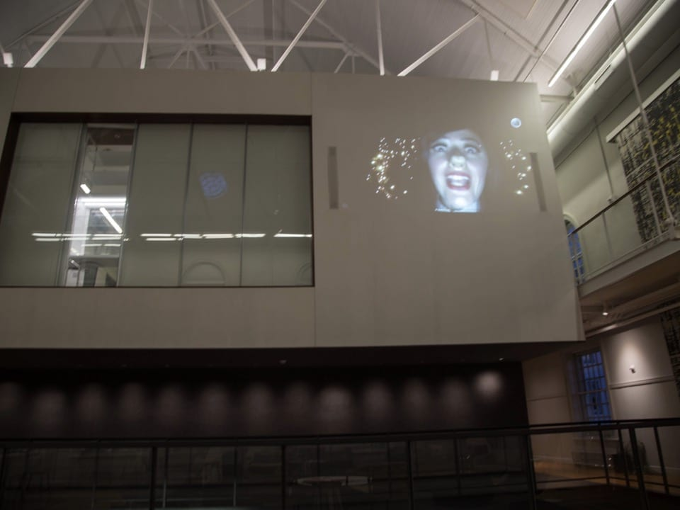 Artist Korallia Stergides is projected onto the wall in VCAM.