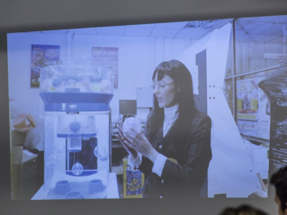 One of the video installations, showing a woman onscreen holding a glass ball
