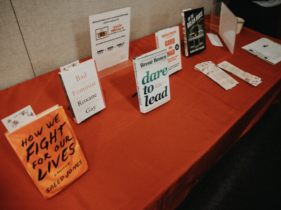 Copies of the suggested books on a long table with a red tablecloth