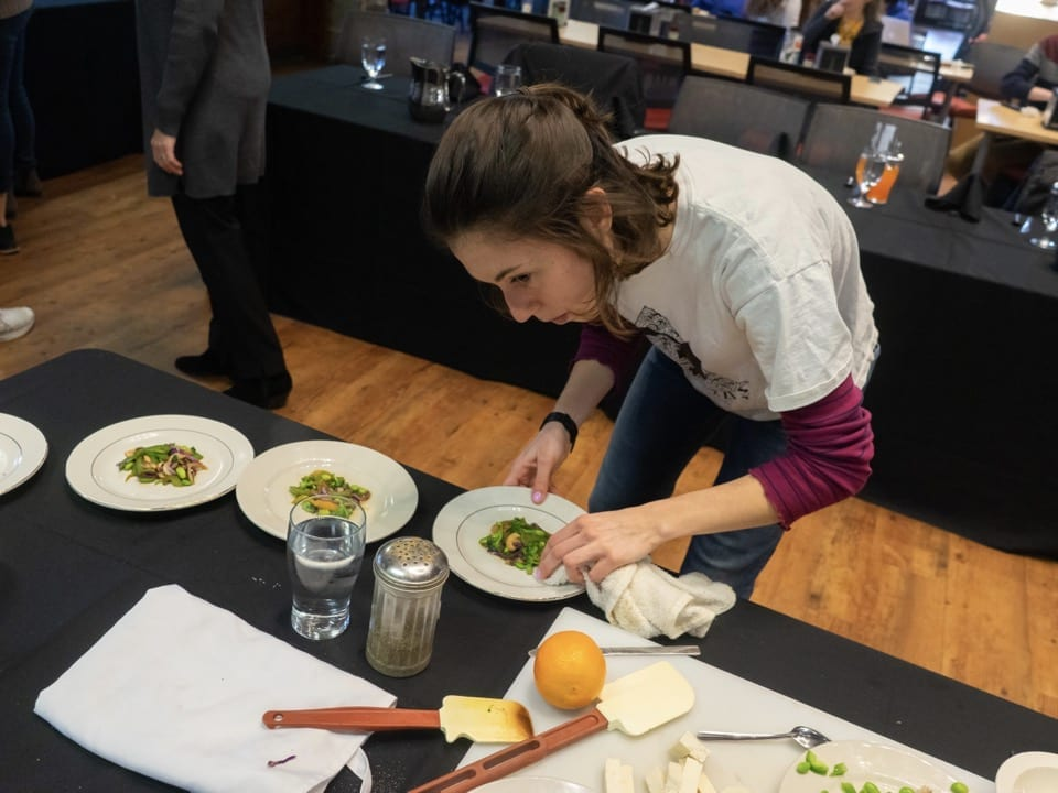 A student uses a rag to wipe the rim of the plates before serving her entree to the judges