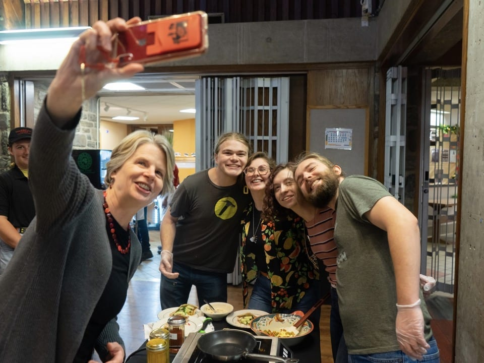 President Wendy Raymond takes a selfie with the four students in the winning team
