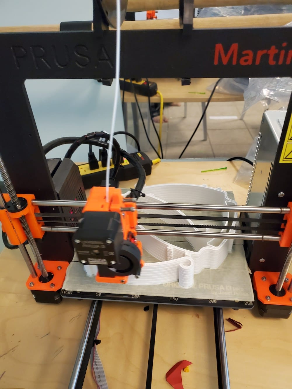 A 3D printer making white headbands for face shields.