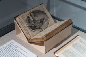 "Frontispiece of Phillis Wheatley's ""Poems on Various Subjects, Religious and Moral"" on display in a glass case"