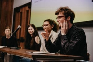 Three students and their professor, Sarah Wilma Watson, seated at a table in front of microphones, speaking on a panel.