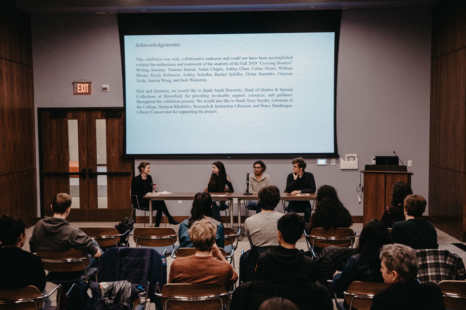 Sarah Wilma Watson, Rachel Schiffer '23, Natasha Bansal '23, and Aidan Chapin seated at a table under a screen with printed acknowledgements for the exhibit in front of a crowd in Lutnick Library
