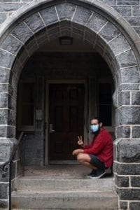 A student sits beneath the arch at Barclay hall flashing a peace sign