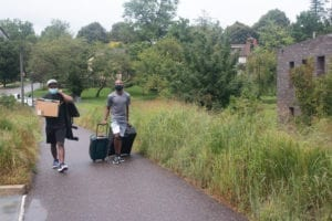 A student wheels a suitcase up the hill at Tritton Hall while his dad carries a box.