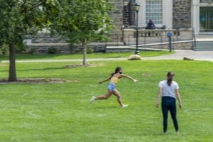 Masked students play Frisbee on Founders Green.