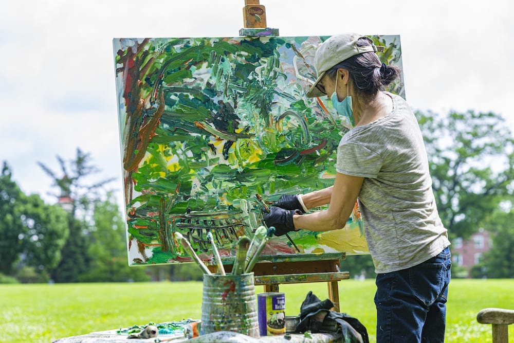 Ying Li, wearing a mask and hat, paints outside by the Duck Pond.