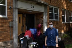 A student standing in front of the Haverford College Apartments with all their bags, including a skateboard and a cello