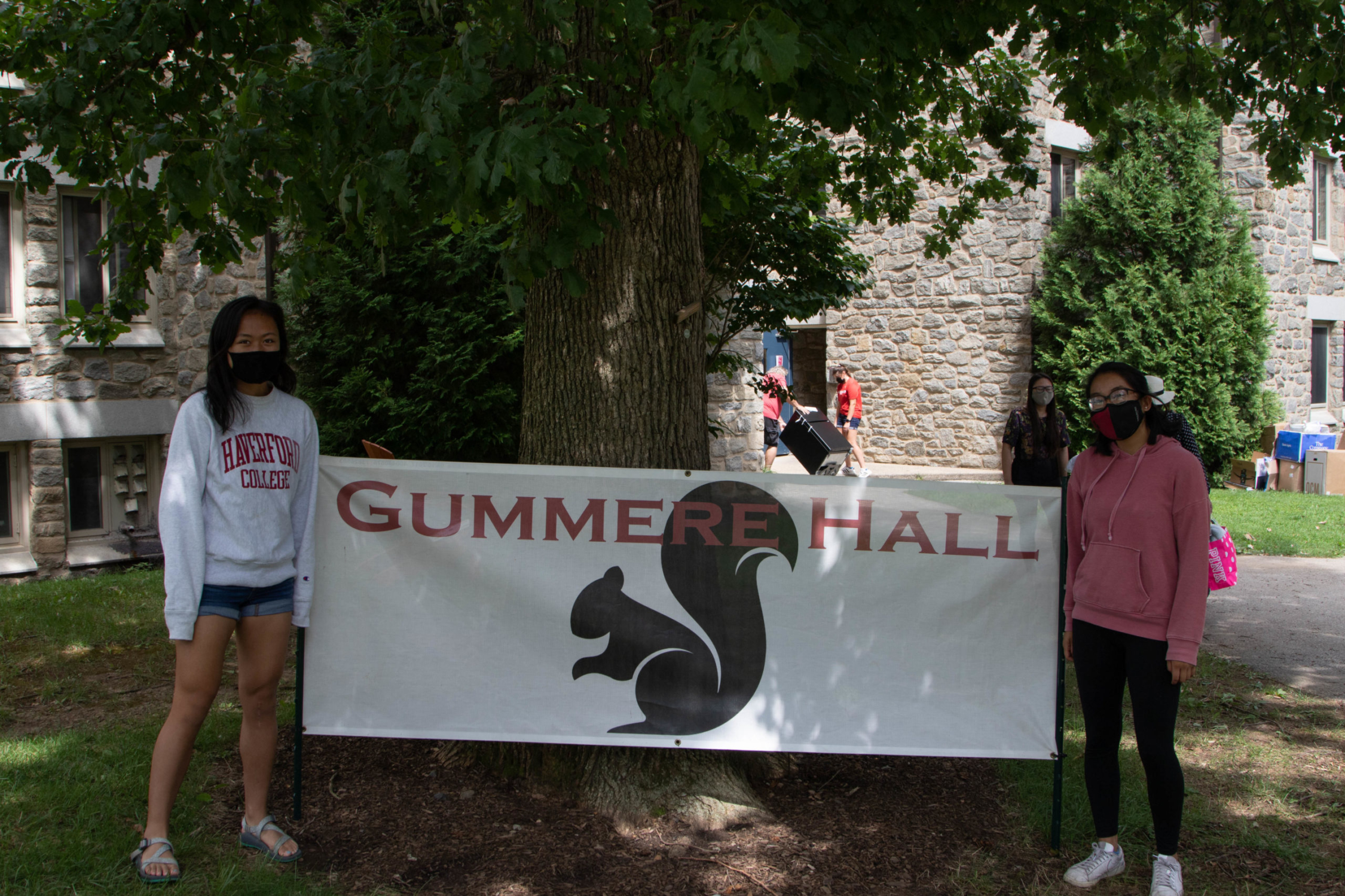 Two students wear Haverford masks and stand in front of a sign that reads Gummere Hall