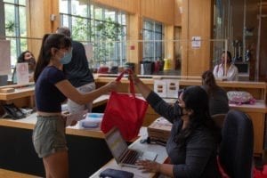 A masked student gets her welcome bag from Michelle Leao in the GIAC.