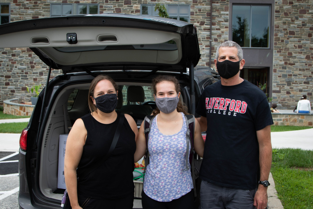 A student and her family, wearing masks and a Haverford t-shirt, pose in front of the car they are unpacking.