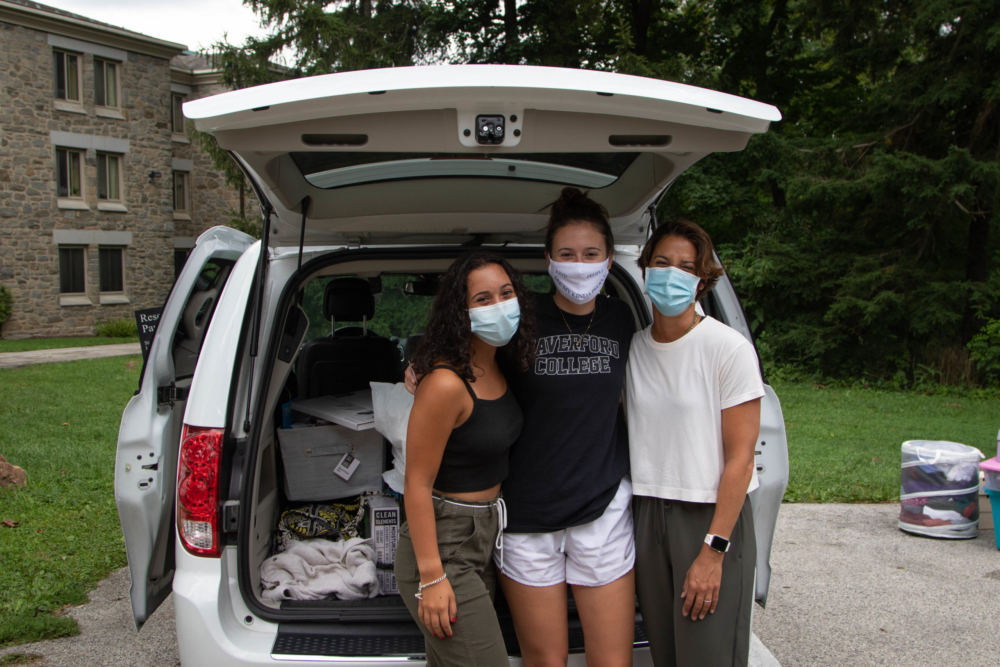 A student in a Haverford College t-shirt posts with her family in front of the car they are unloading near Gummere Hall