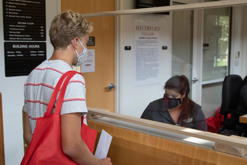 A student checks in at the GIAC; a masked woman behind glass gets his keys