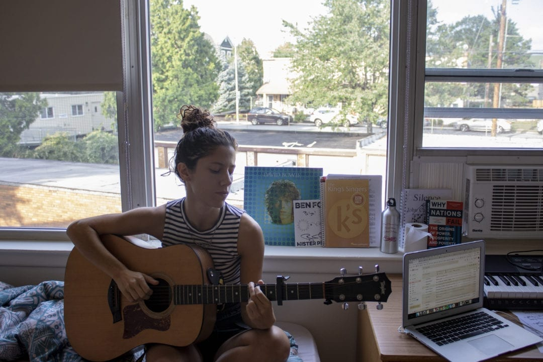 Bilge Nur Yilmaz plays acoustic guitar sitting on her bed next to her open laptop and in front of a David Bowie record