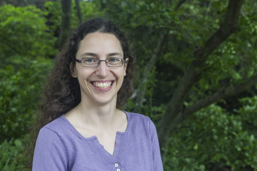 Sarah Horowitz, wearing a purple shirt and glasses, stands in front of a green tree on the Haverford campus