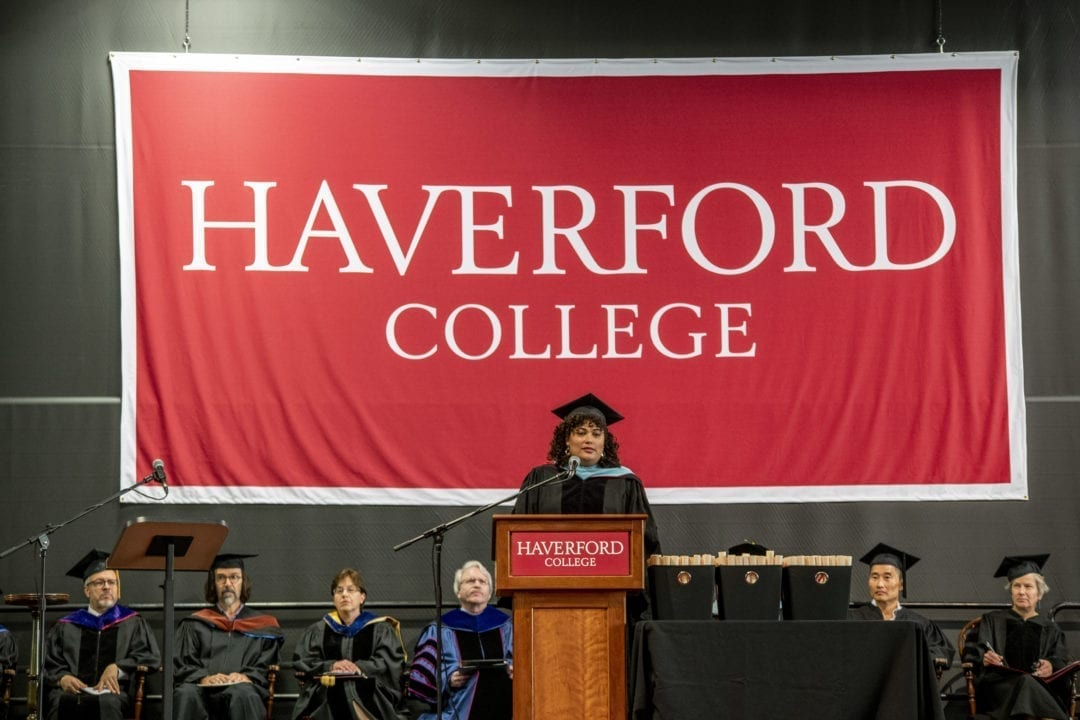 Raquel Esteves-Joyce speaking at a podium in front of a large, red Haverford College sign on the stage at Commencement
