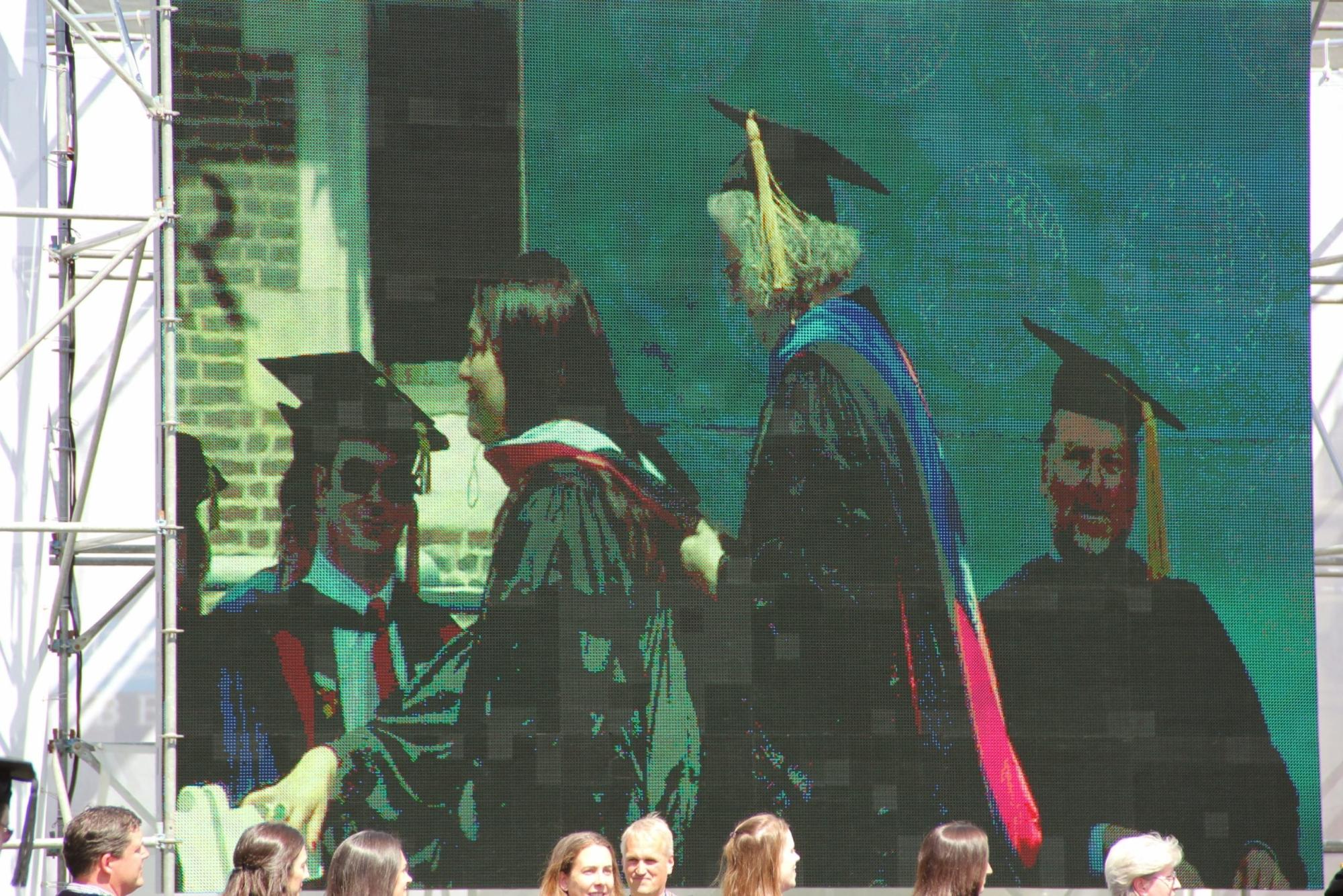 Raquel Esteves-Joyce being hooded on the jumbotron at her Ph.D. graduation