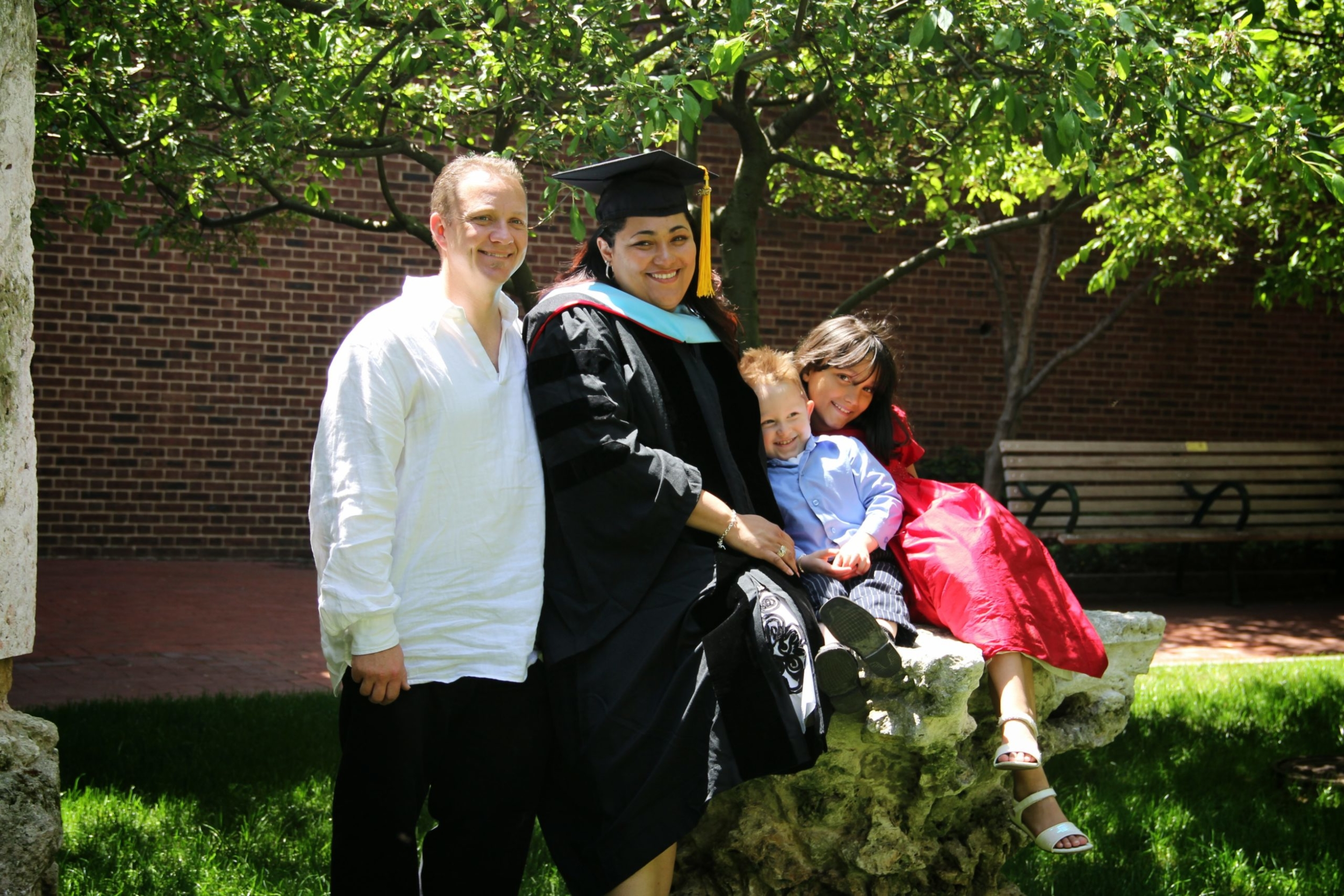 Raquel Esteves-Joyce in a cap and gown and hood poses with her husband and two small children after her graduation ceremony