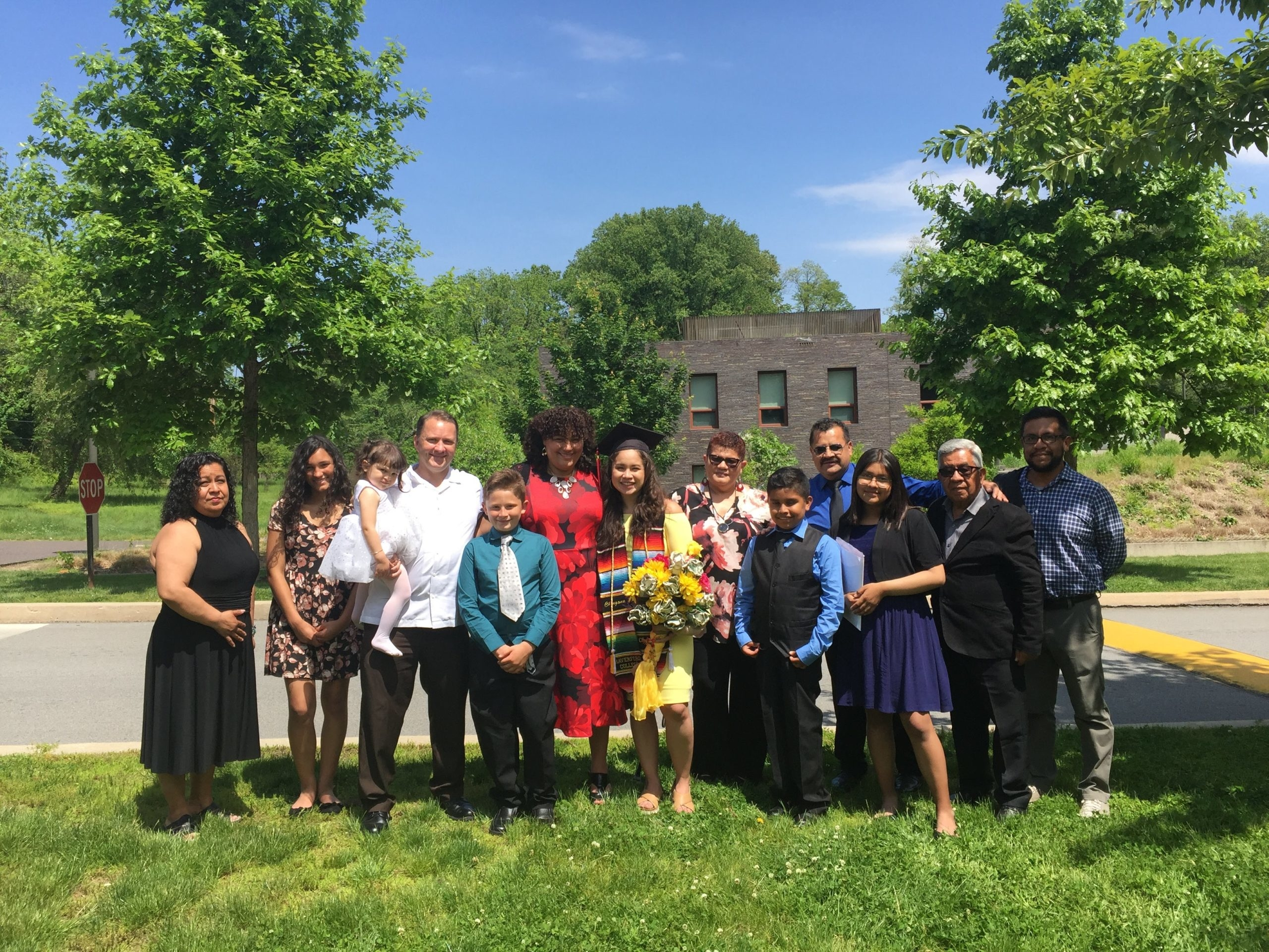 Raquel and Tania, who is holding a big bouquet of flowers and wearing a graduation cap, stand in a line with their family members on Haverford's campus