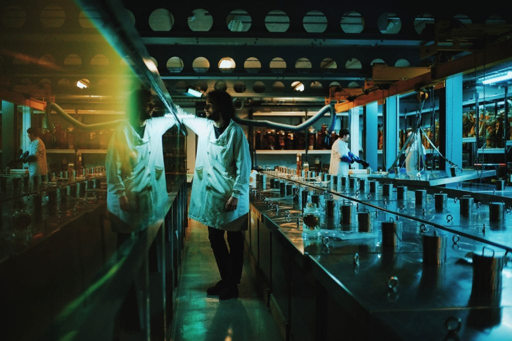 A still from Leviathan Cycle with two people in lab coats in a wet lab