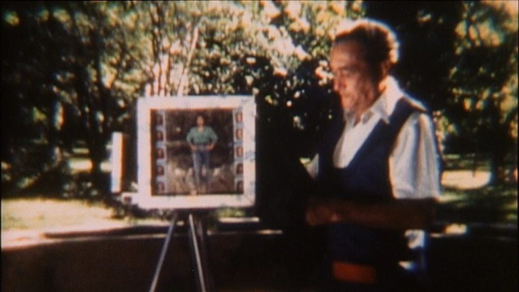 A still from a film in which a man looks at images on a tripod