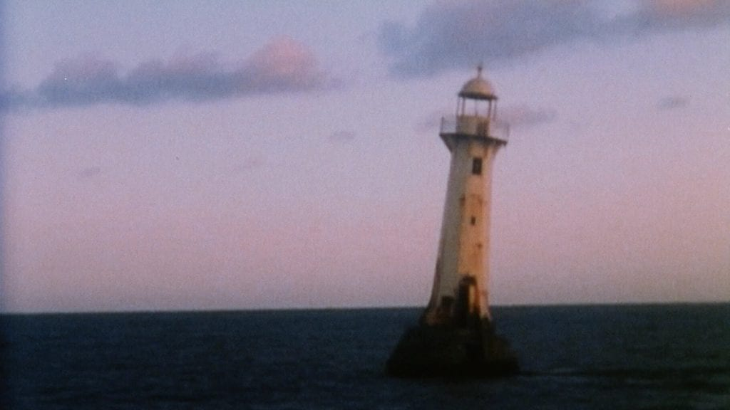 "A still from ""O fim do sem fim"" with a lighthouse against a sunset"