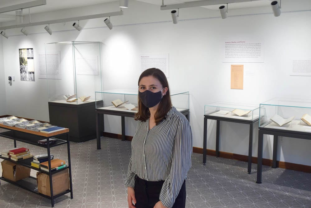 Charlotte Scott, wearing a mask, stands amid display cases in the exhibit she curated in the library