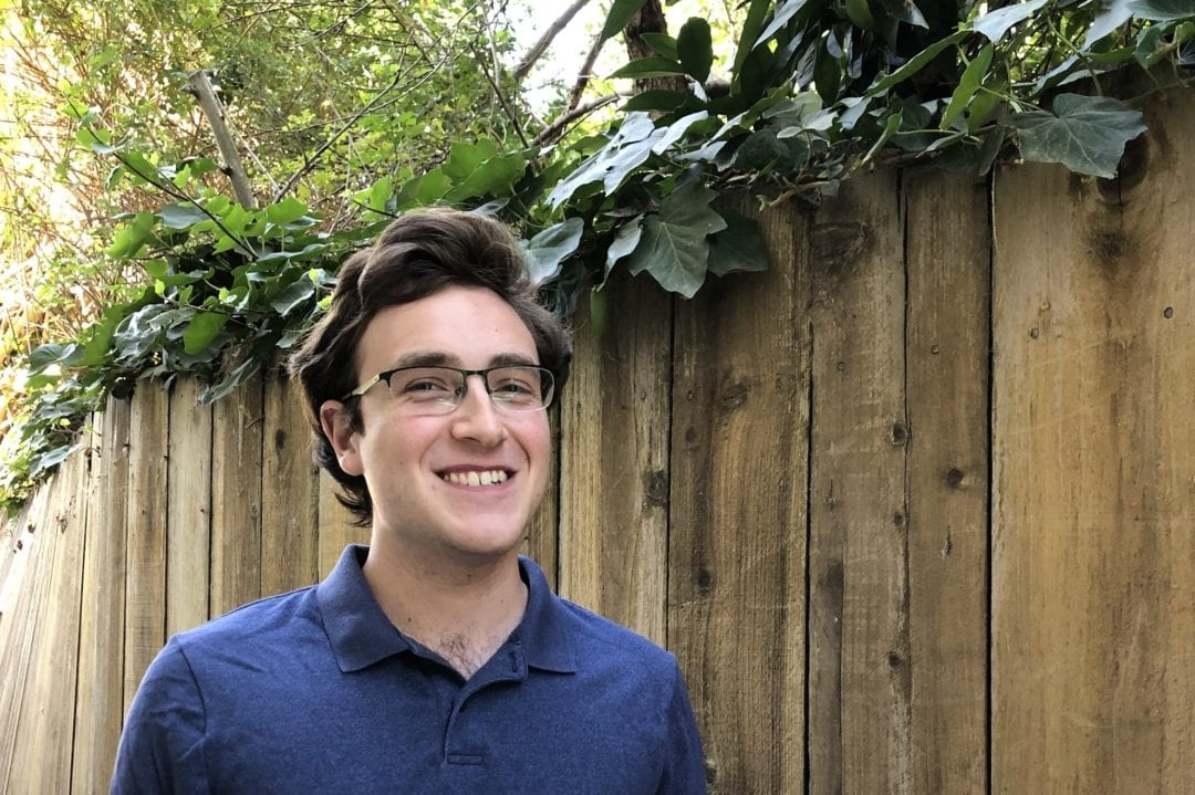 Colin smiles in a blue shirt in front of a wooden fence.