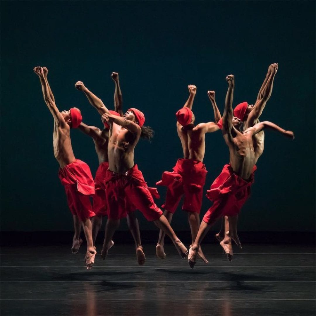 Six men in red headwraps and red wrap pants leap in a circle with one fist up