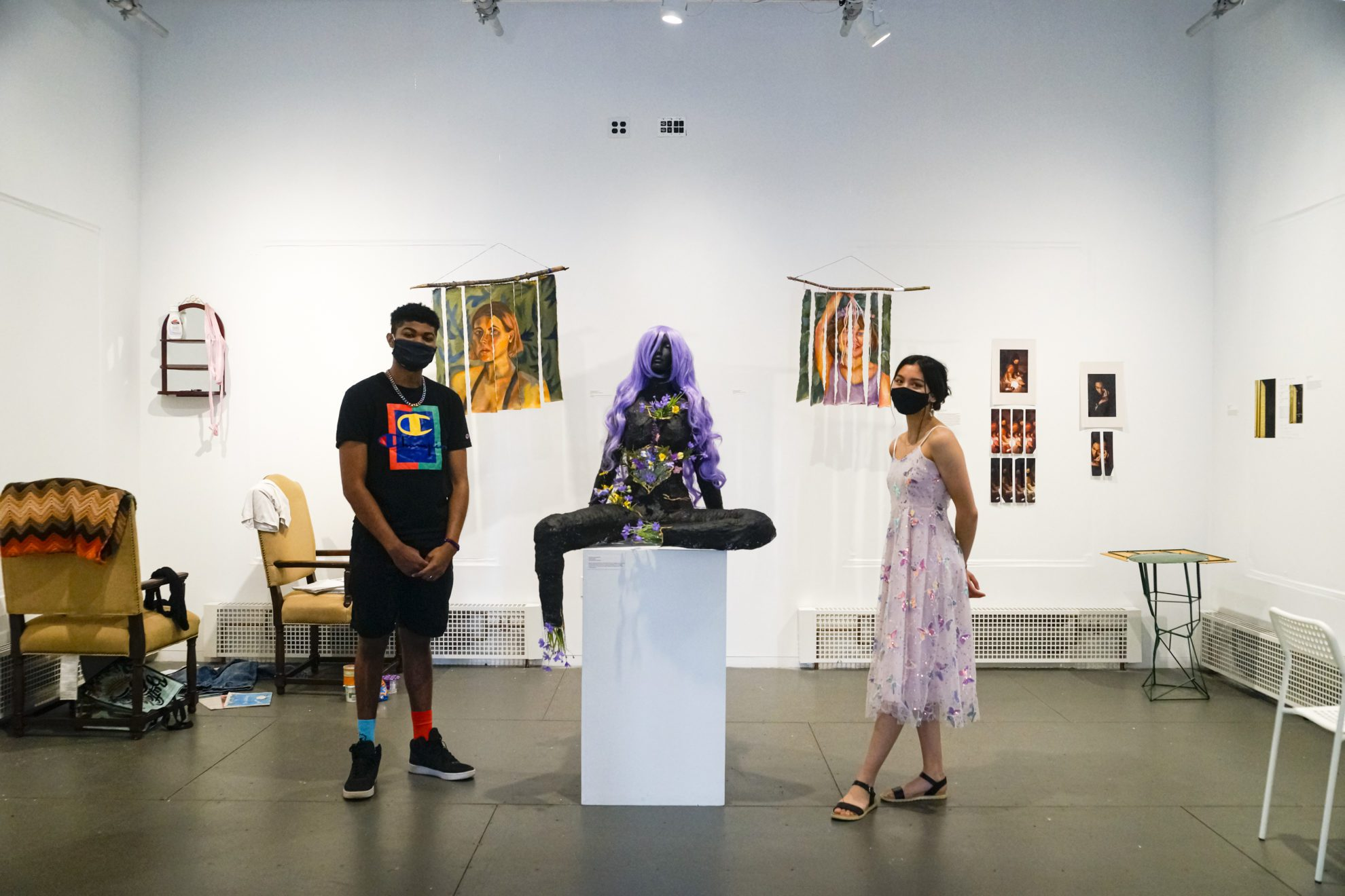 Jalen Martin '23 and Izzy Ray '23 stand in the student art center amidst the art pieces of In the Works, the exhibit they curated together.